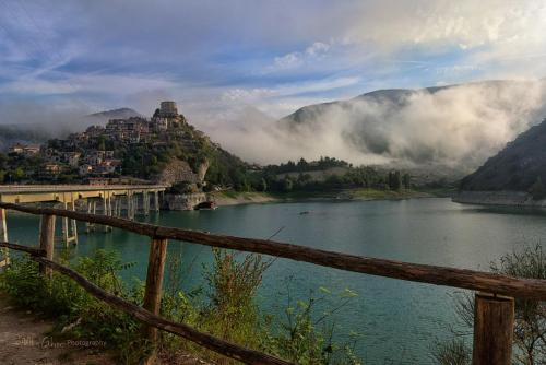 Castel di Tora at sunrise from bridge with low clouds mgpx